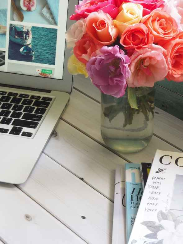 assorted color flower arrangement in clear glass vase beside a laptop
