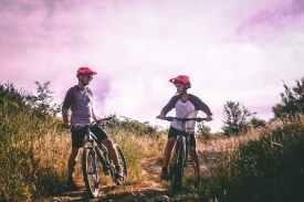 two man riding mountain bike on dirt road at daytime