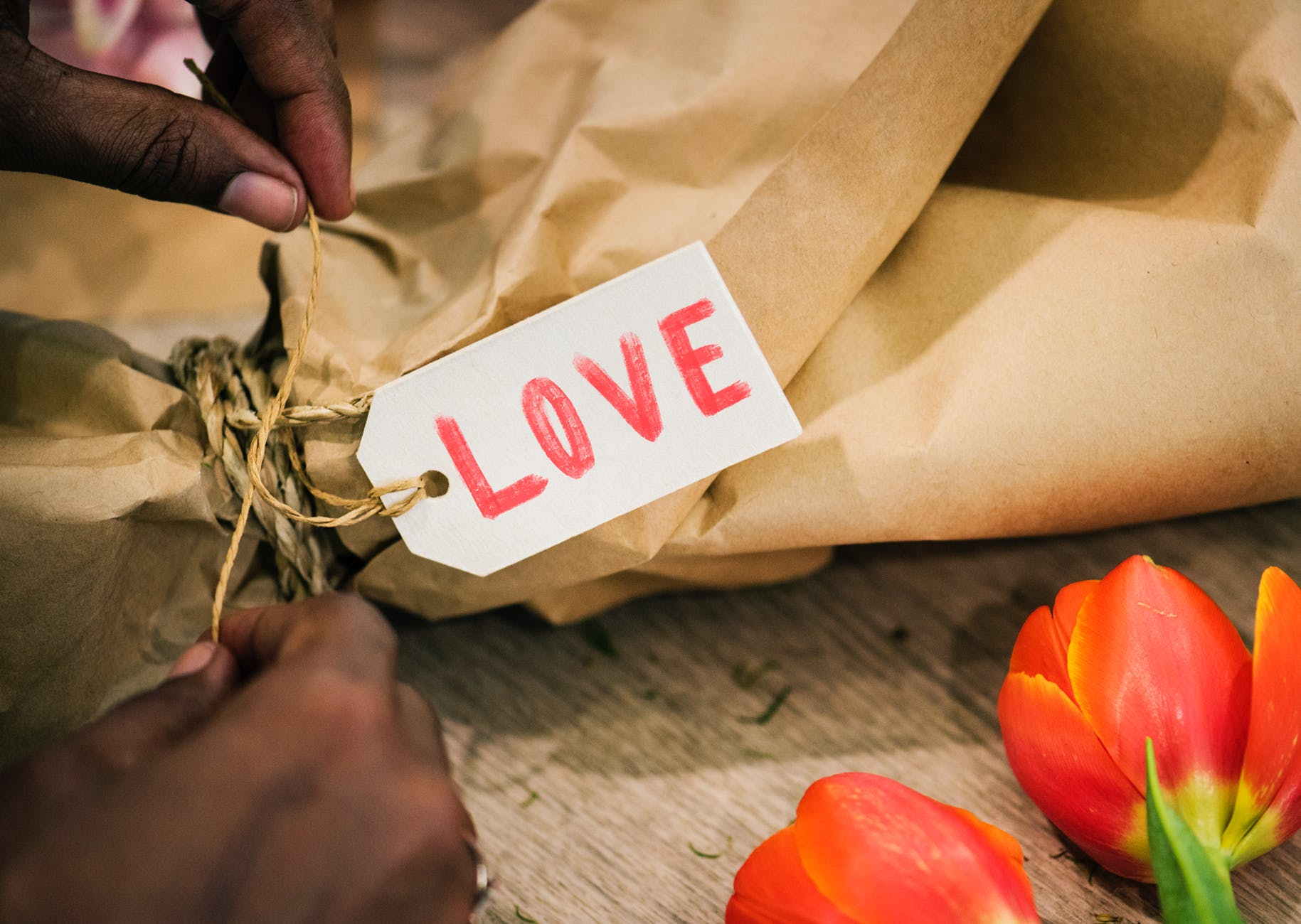 person tying knot on brown paper bag with love tag